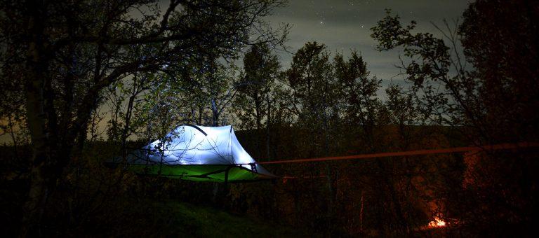 Foto: Hans Ola Østby. Å^sove i et telt slått opp mellom trærne mens du ser på stjernene .